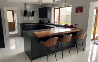 Tavola Kitchen - Hacienda Black Stained Slab Door, Marango Quartz Worktop, Solid Wood Breakfast Bar - 1