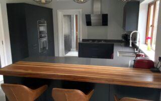 Tavola Kitchen - Hacienda Black Stained Slab Door, Marango Quartz Worktop, Solid Wood Breakfast Bar - 2